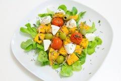 Warme salade met geroosterde pompoen en kersentomaten met eigengemaakte kaas en olijven Stock Afbeelding