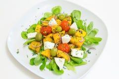 Warme salade met geroosterde pompoen en kersentomaten met eigengemaakte kaas en olijven Stock Foto's