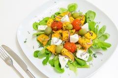 Warme salade met geroosterde pompoen en kersentomaten met eigengemaakte kaas en olijven Stock Afbeeldingen