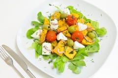 Warme salade met geroosterde pompoen en kersentomaten met eigengemaakte kaas en olijven Royalty-vrije Stock Afbeeldingen