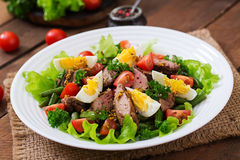 Warme salade met kippenlever, slabonen, eieren, tomaten Stock Foto's