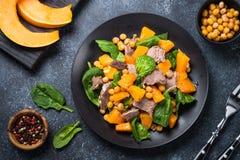 Warme salade met pompoen, gebakken rundvlees, spinazie en kekers stock foto's