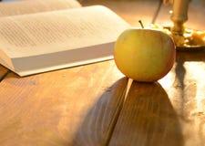 Warme Szene mit offenem Buch und Apfel Stockfoto