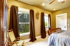 Warme tonenslaapkamer met bruine gordijnen Stock Fotografie
