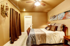 Warme tonenslaapkamer met mooi bed Stock Foto