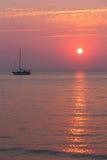 Warme untergehende Sonne u. Segelboot Lizenzfreie Stockfotografie
