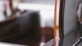 Warme vloeibare chocolade in Chocolade aanmakende machine De mening van de close-up blur stock footage