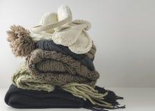 Warme woolen gestrickte Winter- und Herbstkleidung, gefaltet in einem Stapel auf einer weißen Tabelle Strickjacken, Schals, Hands stockfotografie