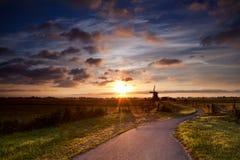 Warme zonnestralen door Nederlandse windmolen stock foto