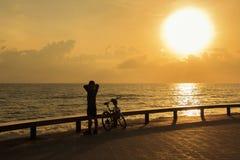 Warmer Abstieg des einzelnen Mannes, nachdem Fahrrad im Park nahe dem Meer am Morgen gefahren worden ist; Songkhla-Provinz, Thail Lizenzfreie Stockfotos