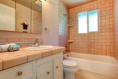 Warmer Badezimmerinnenraum im hellen Pfirsich Stockbilder