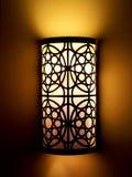 Warmer heller Lampenschirm auf Wand in der Dunkelheit Stockfotografie