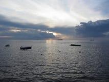 Warmer Seesonnenuntergang mit Frachtschiffen und kleinen Fischerbooten am Horizont Giants-Cumulonimbuswolken sind im Himmel Toska Lizenzfreie Stockbilder