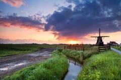 Warmer Sonnenaufgang über niederländischer Windmühle und Fluss Stockfotos