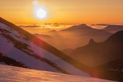 warmer Sonnenaufgang im schneebedeckten Tal stockfotografie