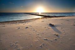 Warmer Sonnenuntergang über Sandstrand auf Nordsee Stockfotografie