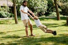 Warmer sonniger Tag Netter kleiner Junge mit seinem Vater in den weißen T-Shirts sind das Spielen im Freien Vater kreist Sohn her stockfotos