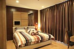 Warmer Ton der Luxusinnenarchitektur des Schlafzimmers im Kondominium, als Hintergrund Stockbilder
