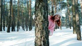 Warmer und glücklicher Winter, nettes Mädchen, das in Wald, eine Frau mit dem roten Haar, herum laufend in den Schnee geht stock video