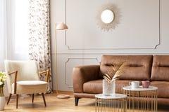 Warmer Wohnzimmerinnenraum mit einem ledernen Sofa, einem Lehnsessel, einer Lampe und Couchtischen mit einem Vase stockfotos