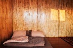 Warmes gemütliches hölzernes Wandschlafzimmer mit einfachem Futon auf dem Boden, Lo Lizenzfreie Stockfotografie