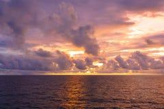 Warmes Licht des brennenden orange Sonnenunterganghimmels mit Wolken, Stockbilder