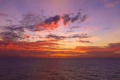 Warmes Licht des brennenden orange Sonnenunterganghimmels mit Wolken und Meer, Beautifu Stockfoto