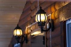 Warmes Licht von externen Lampen auf der Hausmauer Stockbilder