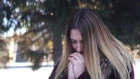 Warmes lindos de la muchacha sus manos con su boca al aire libre en tiempo frío almacen de metraje de vídeo