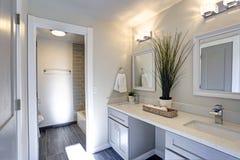 Warmes und sauberes Badezimmer mit grauem doppeltem Eitelkeitskabinett lizenzfreie stockbilder