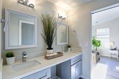 Warmes und sauberes Badezimmer mit grauem doppeltem Eitelkeitskabinett stockfotografie