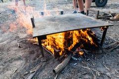 Warmhoudplaat die over een kampbrand klaar opwarmen voor het koken royalty-vrije stock foto's