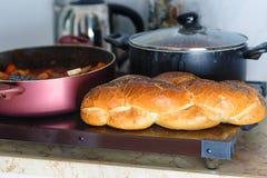Warmhoudplaat voor Sabbat of Sabbat met cholent of Hamin in Hebreeuwse, kruidige vissen en challah-speciaal brood in Joodse keuke stock fotografie