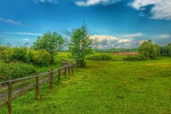 Landscape of Masuria in Poland. Warmian-Masurian region in northern Poland. View on field road, wooden fence and green meadows. village and countryside climate royalty free stock images