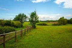 Landscape of Masuria in Poland. Warmian-Masurian region in northern Poland. View on field road, wooden fence and green meadows. village and countryside climate stock images