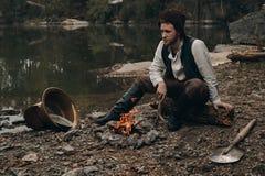 Warmin Unshaved do escavador de ouro acima do fogo próximo no banco rochoso Fotografia de Stock