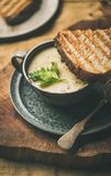 Warming celery cream soup and toast over linen tablecloth, close-up royalty free stock photography