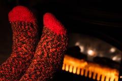 Warming Feet by Fireplace. Warming Feet in Woolen Socks by Fireplace Stock Photos