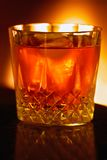 Warming fireside drink, backlit by the light of the fire Stock Photography