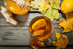 Warming ginger and lemon flavored hot drink or tea. In a transparent cup on a rustic wooden table, surrounded by leaves and a selection of ingredients - lemon Stock Images