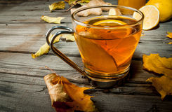 Warming ginger and lemon flavored hot drink or tea. In a transparent cup on a rustic wooden table, surrounded by leaves. Copy space Stock Photography