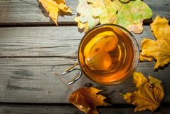 Warming ginger and lemon flavored hot drink or tea. In a transparent cup on a rustic wooden table, surrounded by leaves. Copy space, top view Royalty Free Stock Image