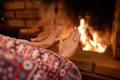 Warming hands. Couple warming hands at fireplace at home stock image