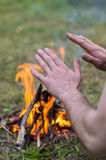 Warming hands by the fire, outdoors Stock Image