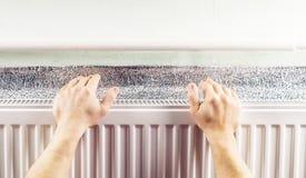 Warming hands near the aluminum radiator Royalty Free Stock Photos