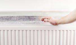 Warming hands near the aluminum radiator Royalty Free Stock Image