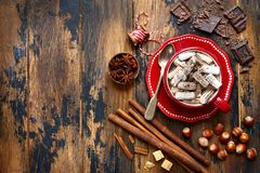 Warming hazelnut hot chocolate with mini marshmallow in a red cu. P over dark old rustic wooden background.Top view with copy space Stock Image