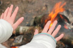Warming his hands near the fire. Child warms his hands near the fire in the tourism campaign. soft focus Stock Images