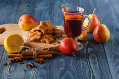 Warming mulled wine with lemon in mug, pile of books Stock Photography
