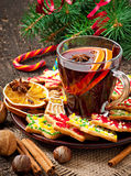 Warming mulled wine, spices and gingerbread cookie. On a wooden background in rustic style stock photo